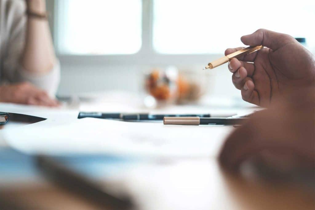 Männliche Hand hält einen Kugelschreiber in der Hand