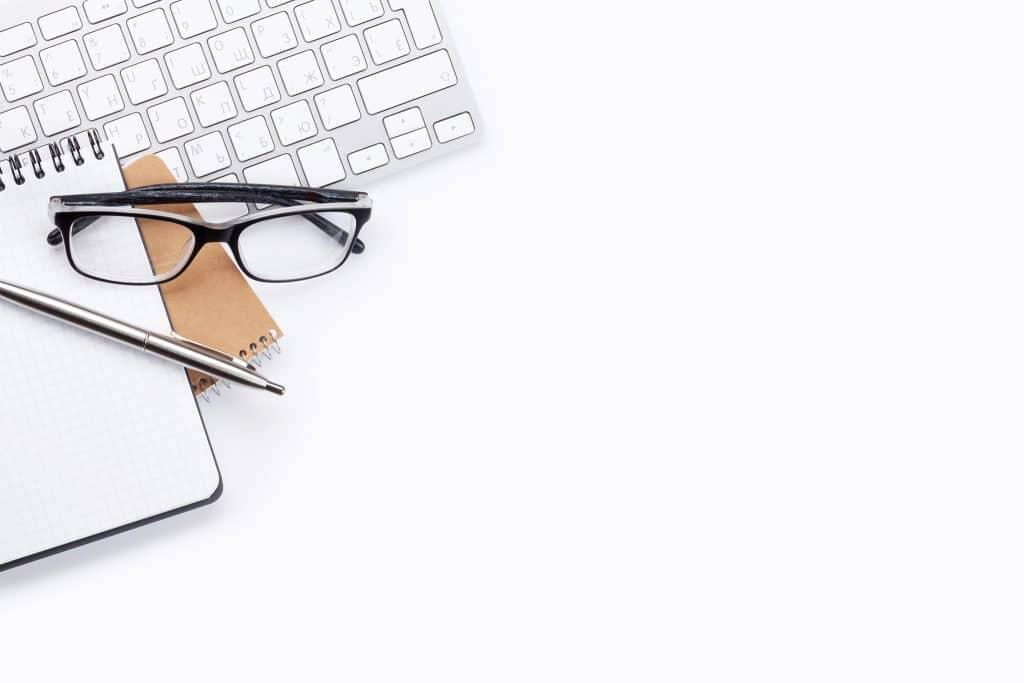 Brille, Block und Computertastatur auf einem weißen Schreibtisch