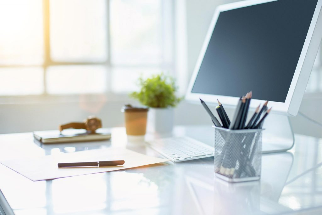 Büroutensilien auf einem Schreibtisch mit Monitor