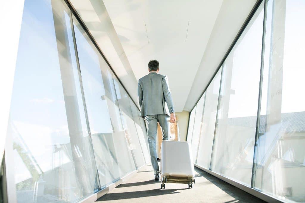 Mann in Anzug zieht einen Reisekoffer